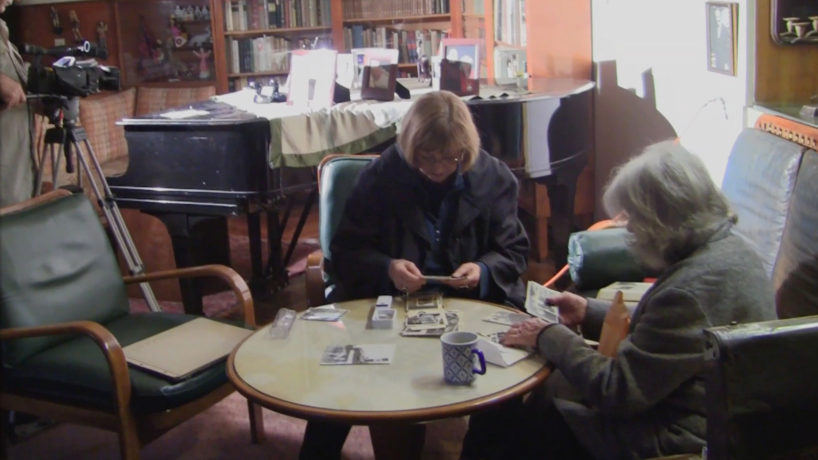 Shooting in Ecuador. The film's director, Eva Zelig, selects photos in the Quito home of a Jewish refugee from Prague.